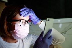 Woman in medicine mask and latex gloves reading news in social media on smartphone, feeling panic about covid-19 coronavirus. Hypochondria and fear of gems concept. Prevention of infection spread