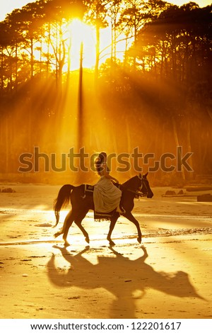 woman in medieval clothing backlit by sunlight on beach - stock photo