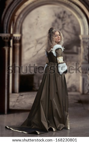 Woman in medieval dress looking back, antique interior background #168230801