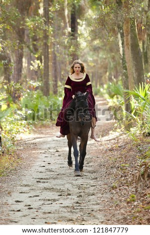 woman in medieval dress riding horseback through forest