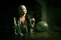 Woman in medieval outfit working as an alchemist or witch in the kitchen of a French medieval castle - with property release
