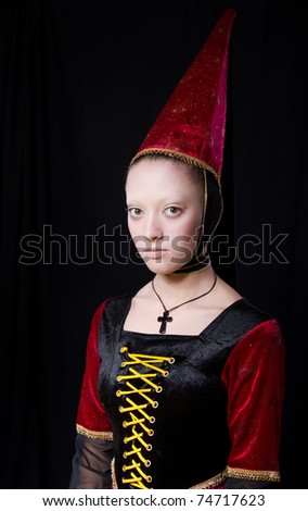 Woman in medieval style historical dress and hat. Over black