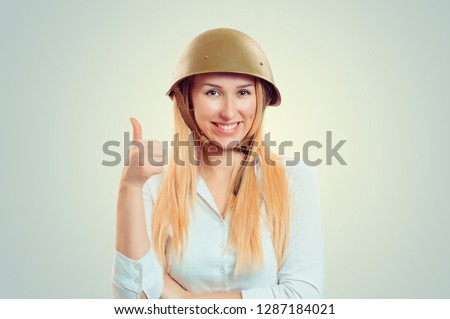 Woman in military armor cap helmet of World War II period showing like thumb up hand gesture. Caucasian person in white formal shirt, long blonde hair isolated on light green yellow studio background