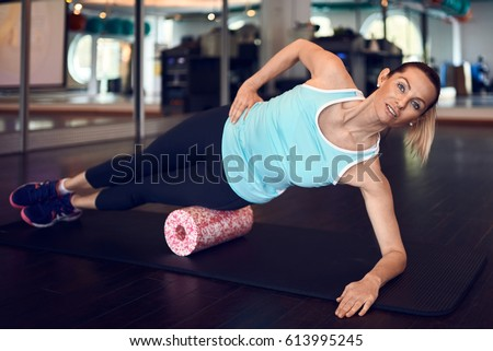 Woman in mint sleeveless shirt and black leggings in gym doing exercise with foam or fascia roll and looking at camera.