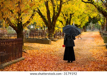 Woman in Mourning at Cemetery in Fall, with Black Umbrella