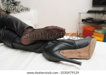Woman in nylon feet and high heel boots