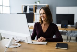 Woman In Office Using Business Computer At Desk