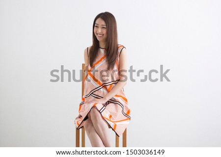 Woman in one piece sitting on a chair