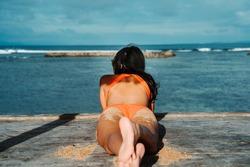 Woman in orange bikini watching seaview from bamboo hut on beach on Gili Air island, off Bali in Indonesia. Close up of beautiful brunette asian woman feet and back in orange thongs on the beach.