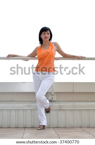 woman in orange blouse standing on a balcony, white background
