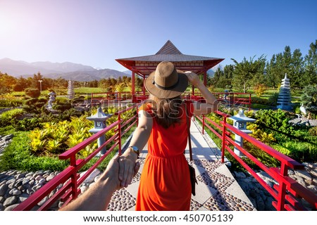 Woman in orange dress and hat holding man by hand going to Japanese Garden with pagoda Foto stock ©