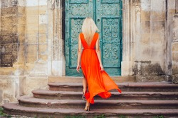Woman in orange dress climbing stairs outdoors in old city. Back view.