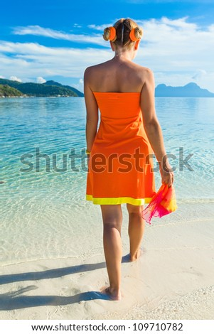 Woman in orange dress on the tropical beach