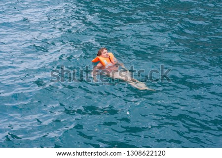 Woman in orange life jacket in water after sport activity. Rescue vintage lifevest object for safe sailing as heathcare element for people.