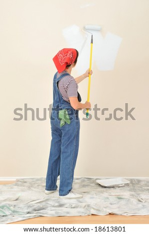 Woman in overalls using paint roller on extension pole painting wall. Viewed form behind the woman is unrecognizable.