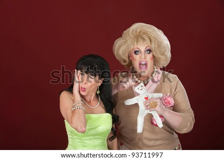 Woman in pain as drag queen sticks a voodoo doll - stock photo