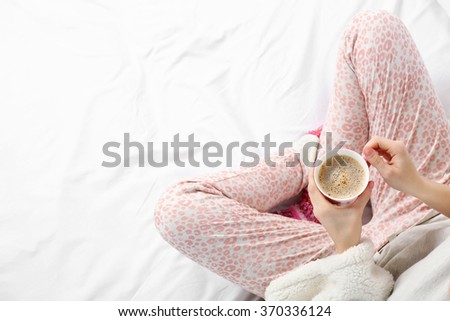 Woman in pajamas holding coffee cup on her bed