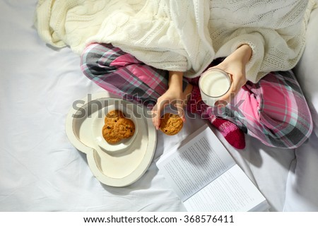 Woman in pajamas reading a book and drinking milk with cookies on her bed
