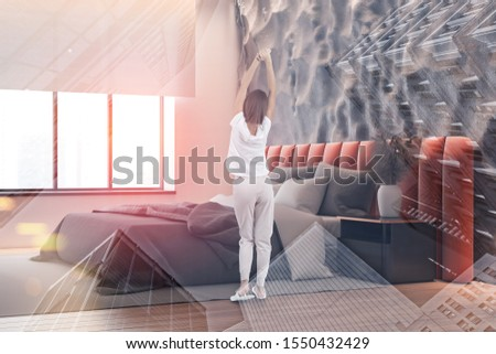 Woman in pajamas standing in modern bedroom with crude gray and pink walls, orange king size bed and black bedside table. Toned image double exposure #1550432429