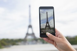 Woman in Paris taking pictures in front of Eiffel Tower, Cell phone
