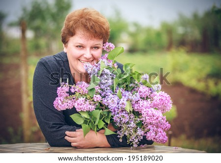 woman in park with a big bouquet of a lilac #195189020
