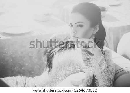Woman in party dress with golden sequins relaxing on sofa in restaurant on sunny day. Holiday celebration and vacation concept #1264698352