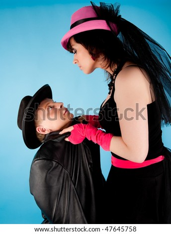 Woman in pink hat and black dress holding the man in black