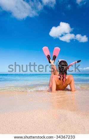 woman in pink snorkel gear on sandy beach