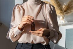 Woman in pink vintage blouse holding serum glass bottle with pipette. Ascorbic Acid, Resveratrol, Caffeine Solution. Hydration of skin and eye contour, trendy colors. Skin care routine concept.