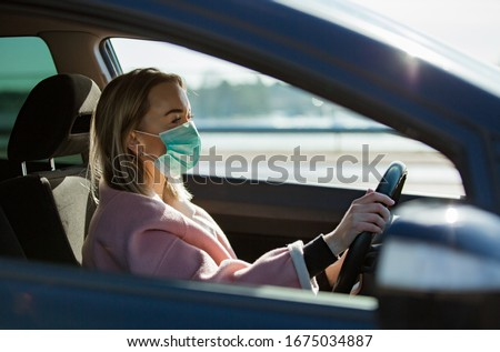 Woman in protective mask driving a car on road. Safe traveling. Foto stock ©