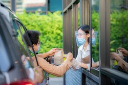 Woman in protective mask taking coffee at drive thru during coronavirus outbreak, Concept for new normal between covid 19 pestilence.