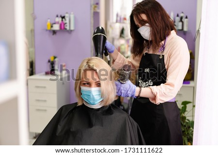 Woman in protective medical mask and hairdresser. Hairdressing salon opened! Covid-19, coronavirus . Quarantine period in city is over! Small business and covid-19, coronavirus
