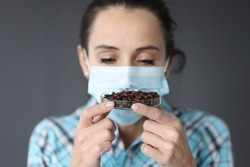 Woman in protective medical mask sniffs coffee grains. Loss of smell in coronavirus concept