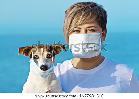 Woman in protective surgical mask holds dog pet in face mask. Chinese Coronavirus disease COVID-19 is dangerous for pets