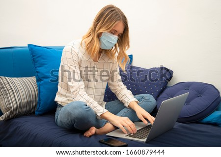 Woman in quarantine for Coronavirus wearing protective mask and smart working