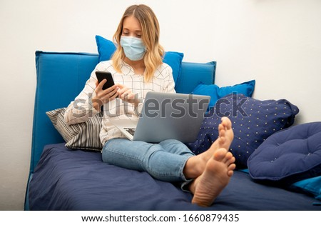 Woman in quarantine wearing protective mask and smart working