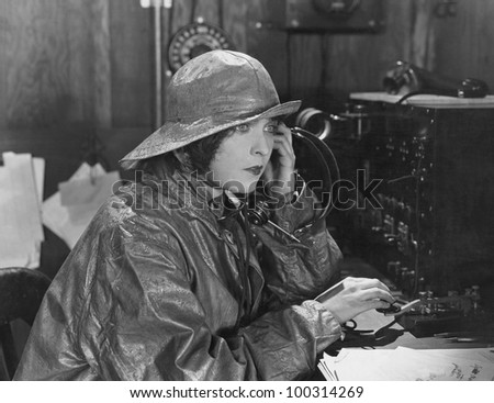 Woman in raincoat sending message in Morse code
