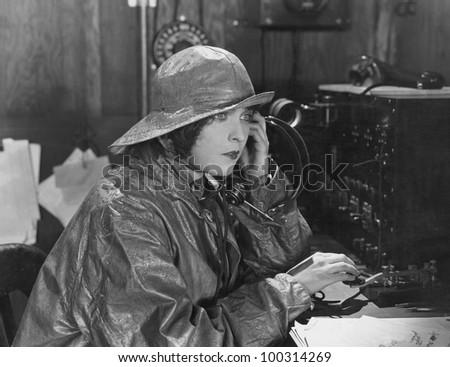 Woman in raincoat sending message in Morse code