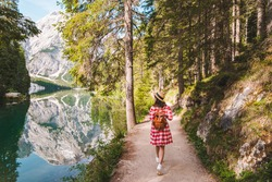 woman in red checkered dress walking around mountain lake. hiking concept. national park lago di braies