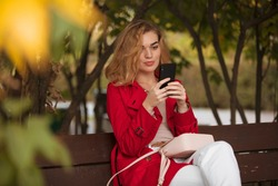 Woman in red coat sitting on a bench with mobile phone messages online sms