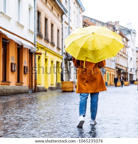 woman in red coat with yellow umbrella walk by street in rainy weather. copy space
