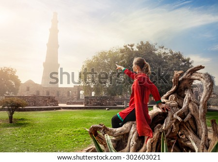 Woman in red costume pointing at Qutub Minar tower in Old Delhi, India ストックフォト ©