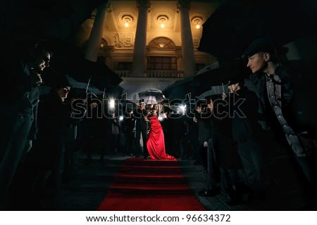 woman in red dress posing in front of paparazzi