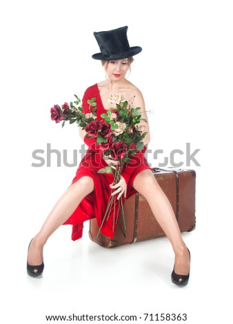 Woman in red dress sitting on a suitcase