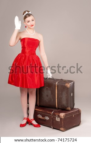 Woman in red dress with old suitcases, waving his hand to leave