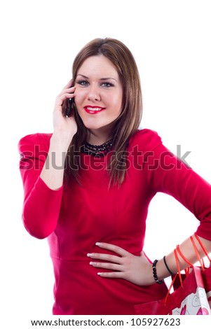 Woman in red dress with shopping bags, smiling and looking directly at the camera while talking on her cellphone