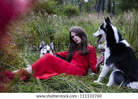 woman in red dress with tree wolfs in forest