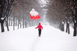 Woman in red during snowstorm goes down the street with bunch of heart-shaped balloons. Sale balloons and requisites for the New year, Valentine's Day and other holidays. Good mood on gray winter day