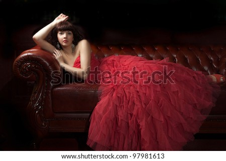 Woman in red evening dress lying on the sofa - stock photo