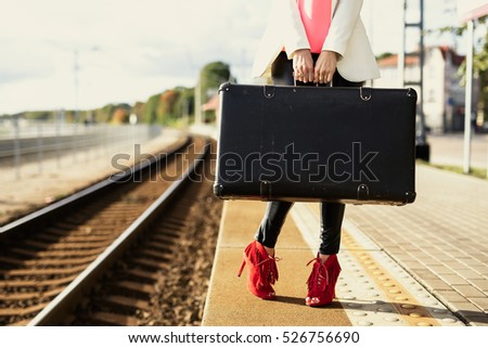 Stock Photo Woman in red high heels waiting in train station and holding suitcase